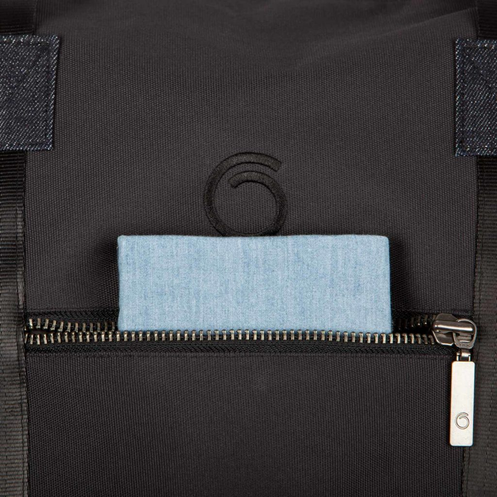 Detail view of the front pocket of the black Weekend Bag with a note book inside