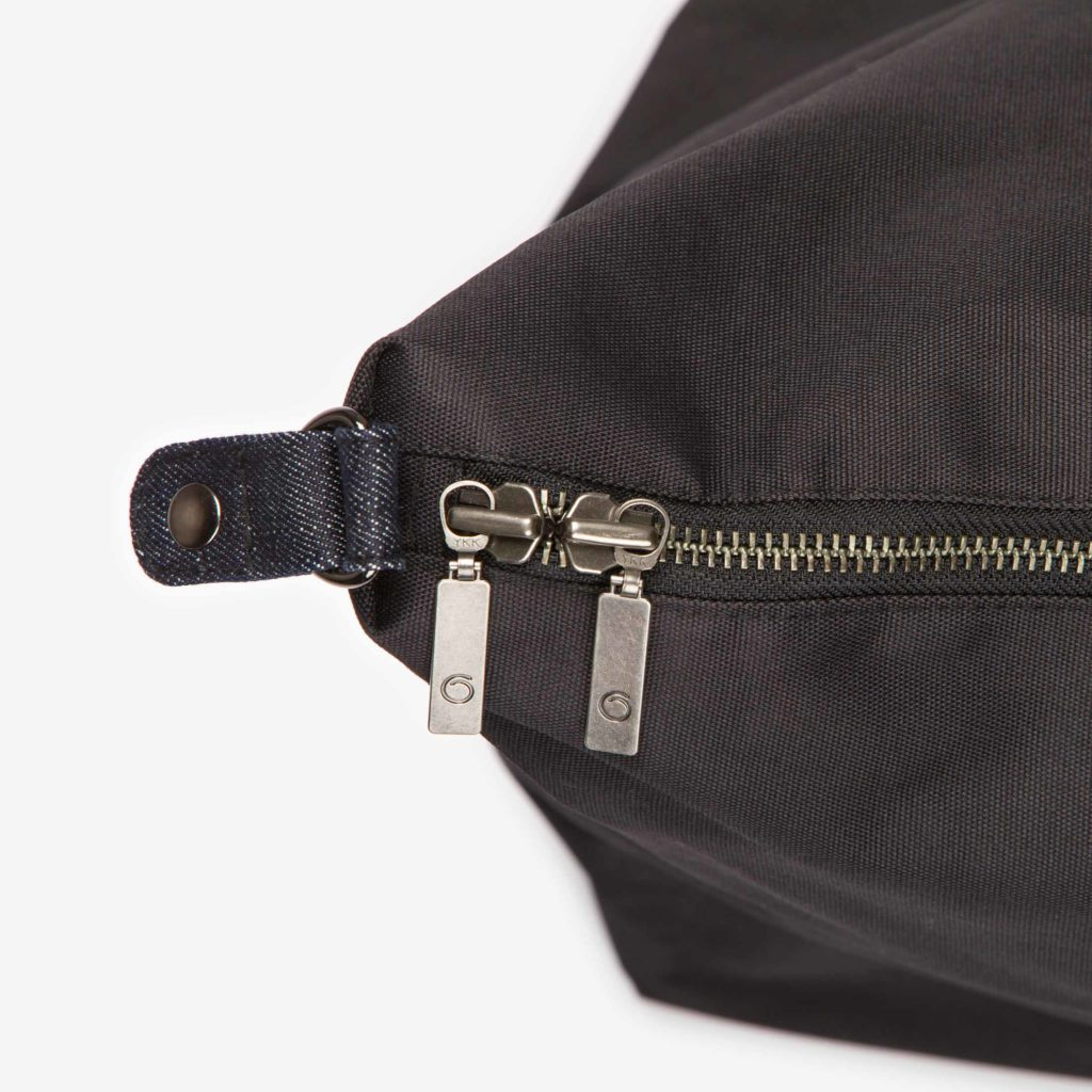 Detail view of the black Weekend Bag showing the double puller zipper and the side button