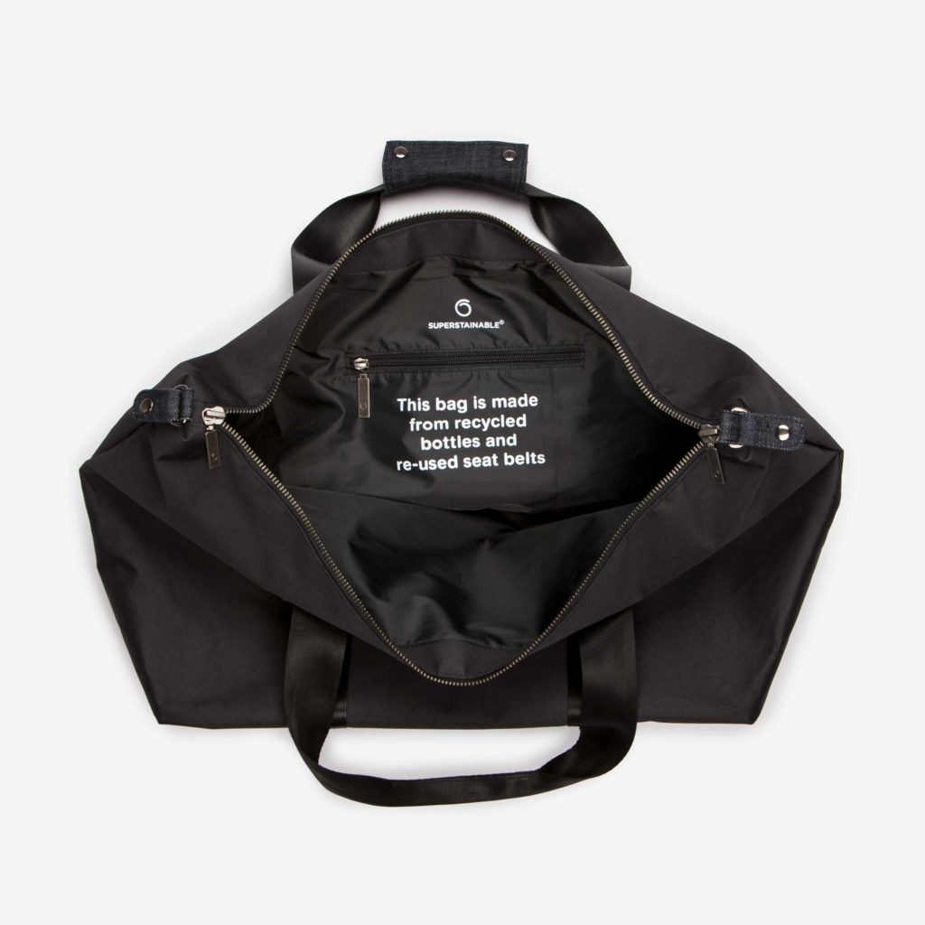 """The open black Weekend Bag showing the inside zipper pocket and the text """"This bag is made from recycled bottles and re-used seat belts"""" written on the inside"""