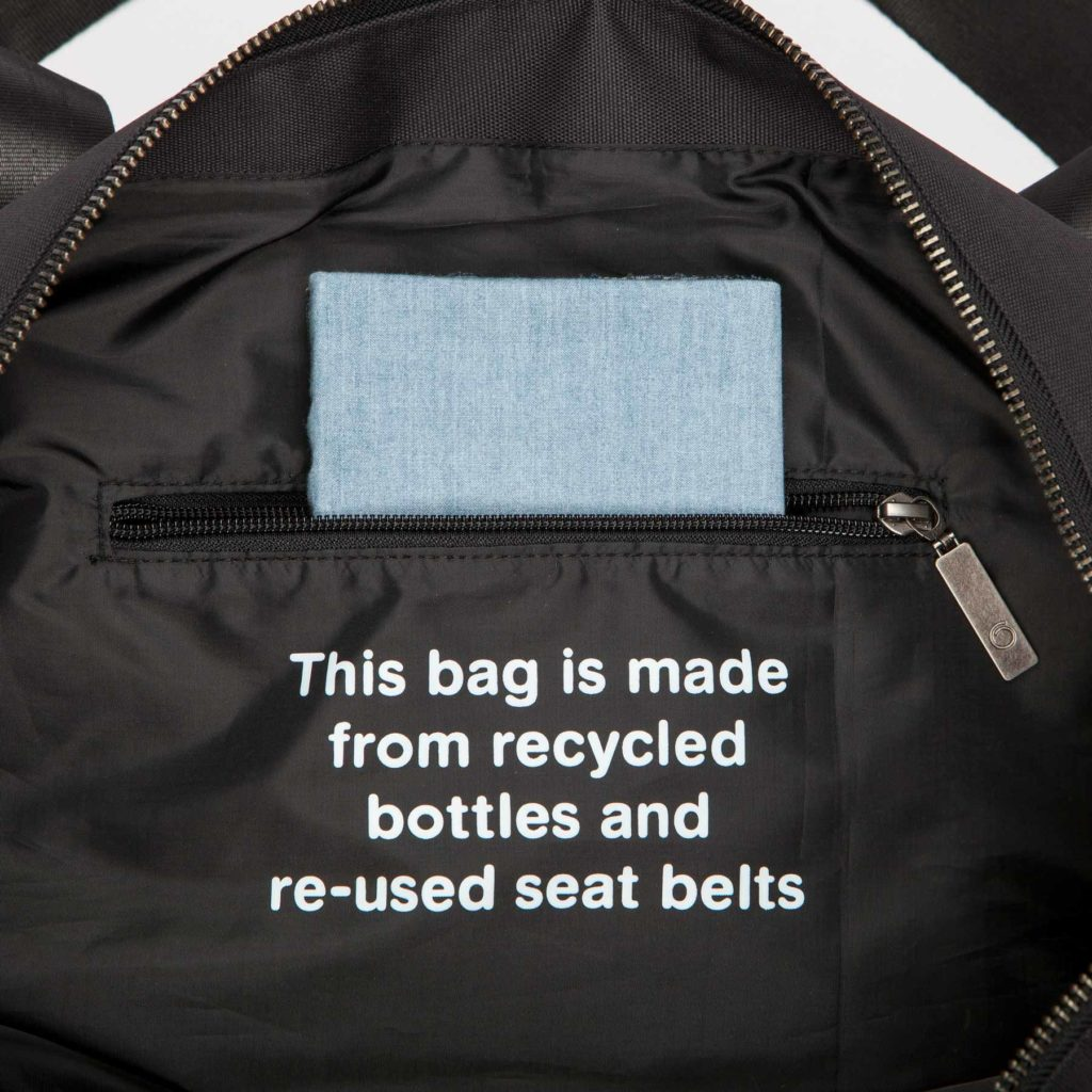 """Detail view of the inside zipper pocket of the black Weekend Bag with the text """"This bag is made from recycled bottles and re-used seat belts"""" written"""