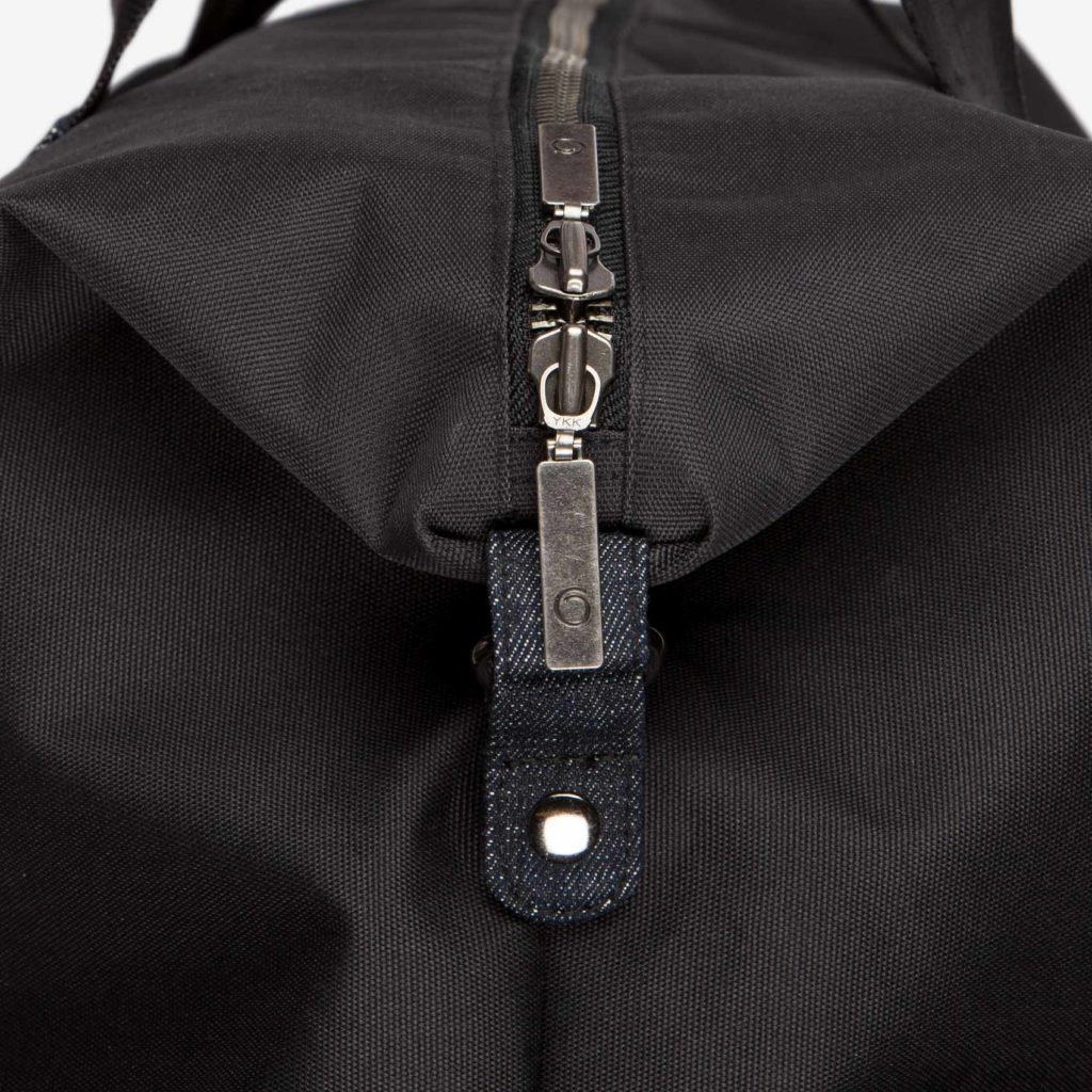Detail view of the top double puller zipper and button of the black Weekend Bag