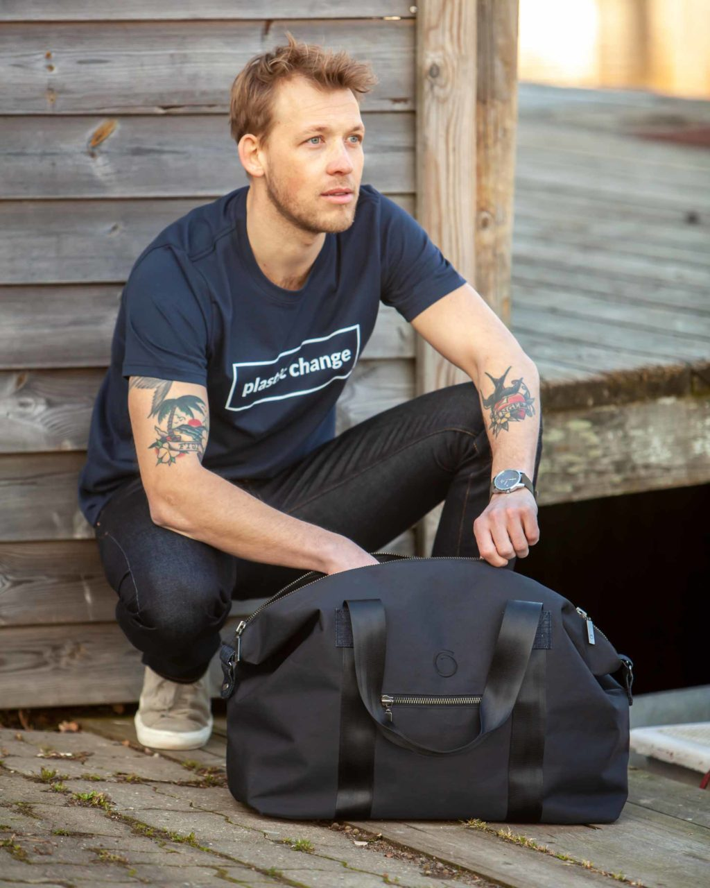 Model sitting next to the black Weekend Bag with one hand inside the bag