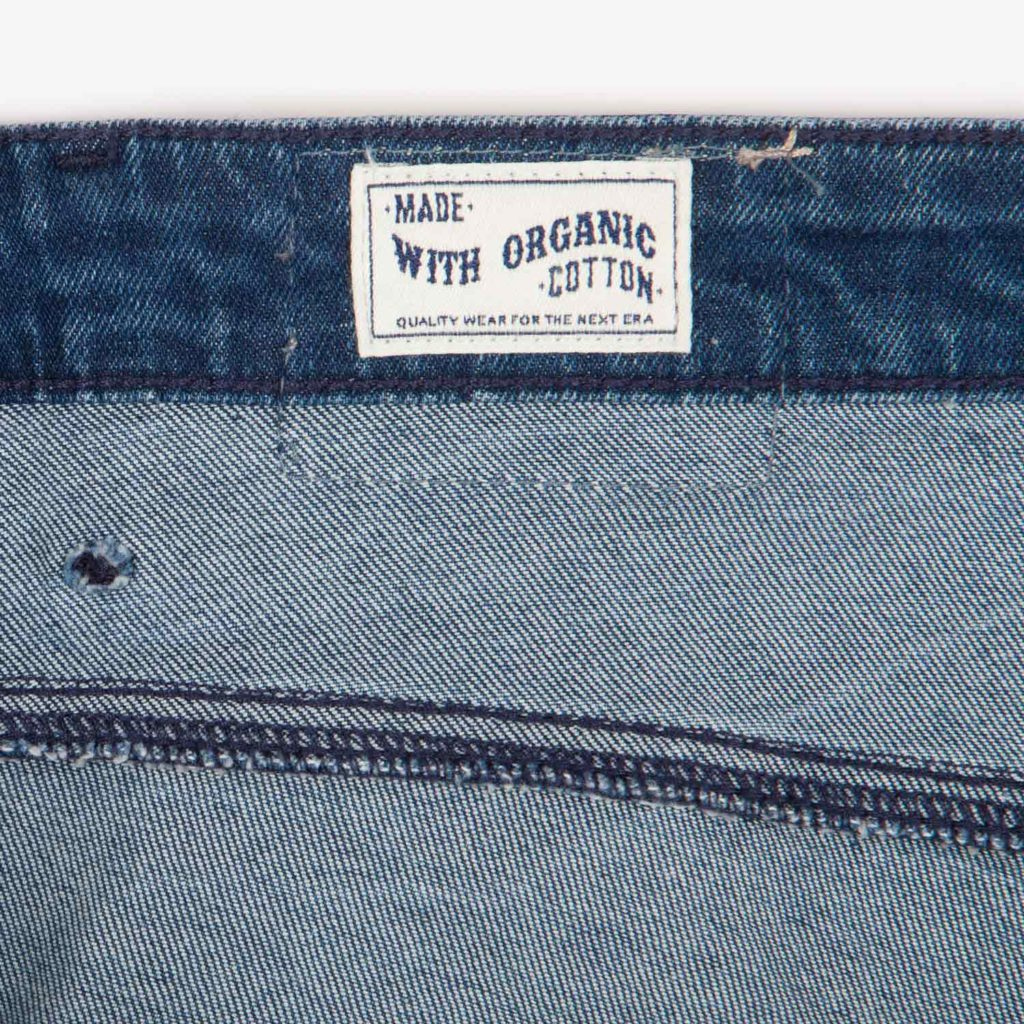 Detail view of the organic cotton label on the Kings of Indigo Christina High jeans