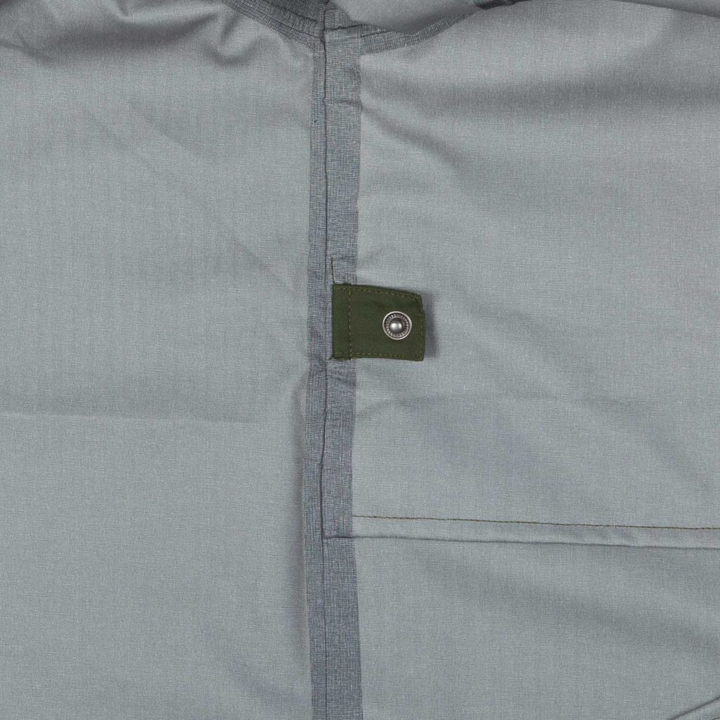 Detail view of the inner button for folding the green Glombak jacket with hood