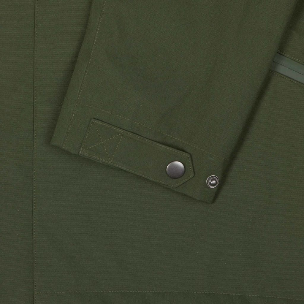 Detail view of the cuff buttons of the green Glombak jacket with hood